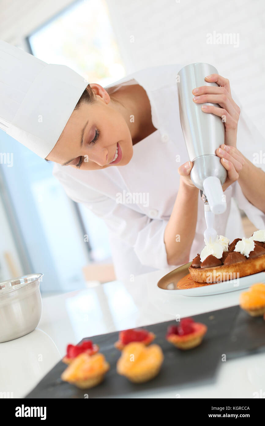 Pastry cook spreading whipped cream on tart - Stock Image