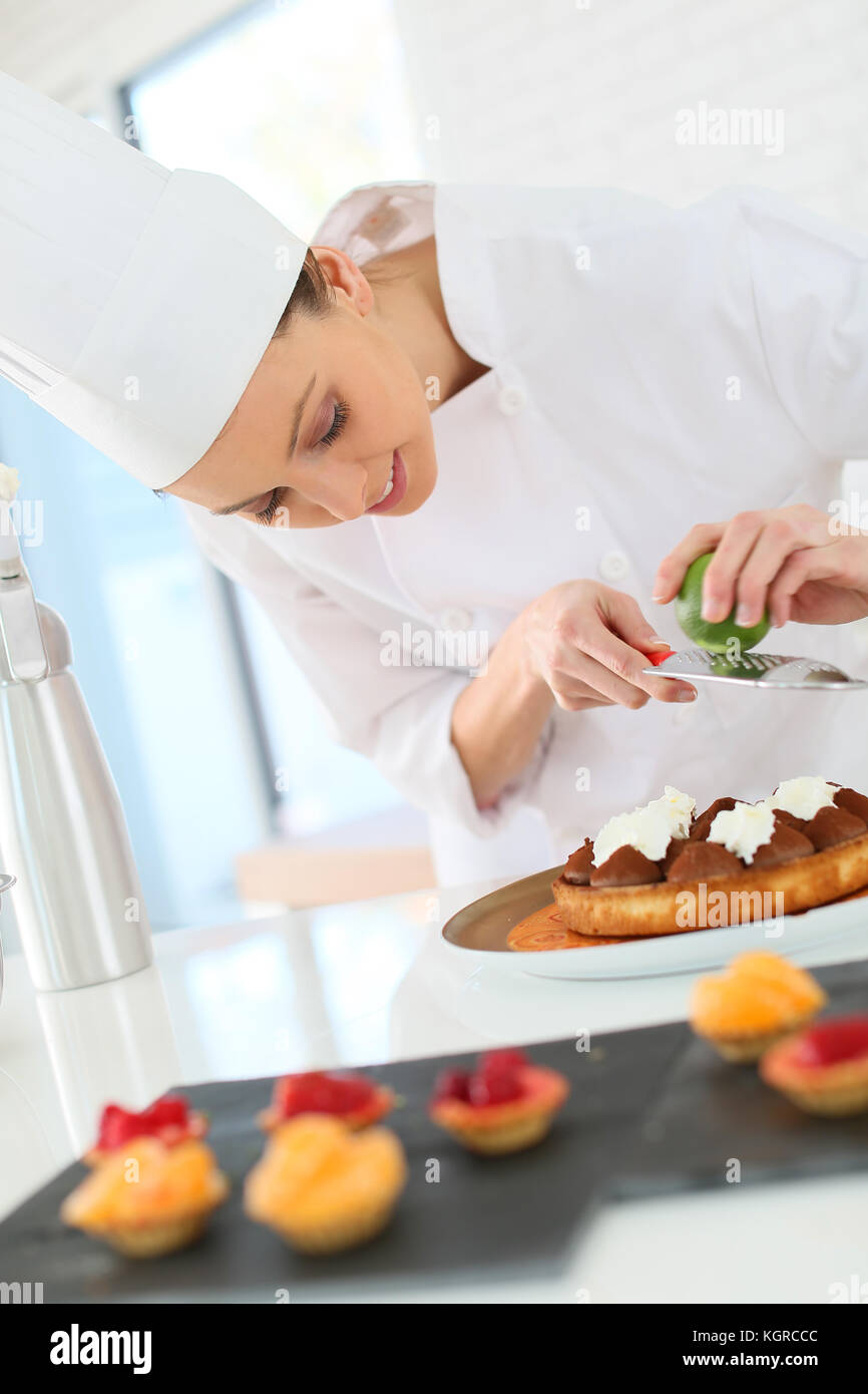Pastry-cook shreding lemon zest over chocolate cake - Stock Image