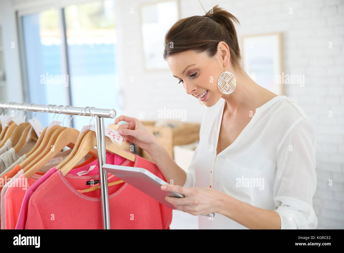 Shop woman preparing summer sales in store - Stock Image