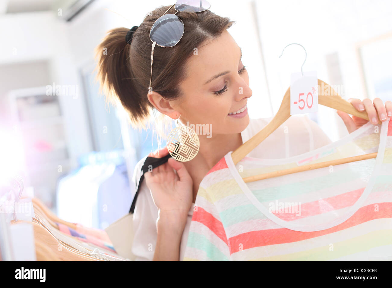 Beautiful woman in clothing storesduring summer sales - Stock Image