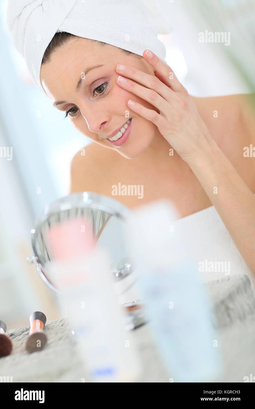 Beautiful woman applying moisturizing cream on her face - Stock Image