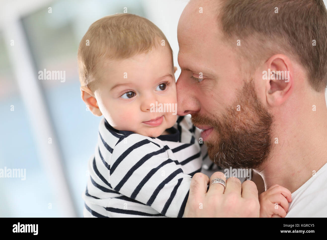 Portrait of daddy embracing baby boy - Stock Image