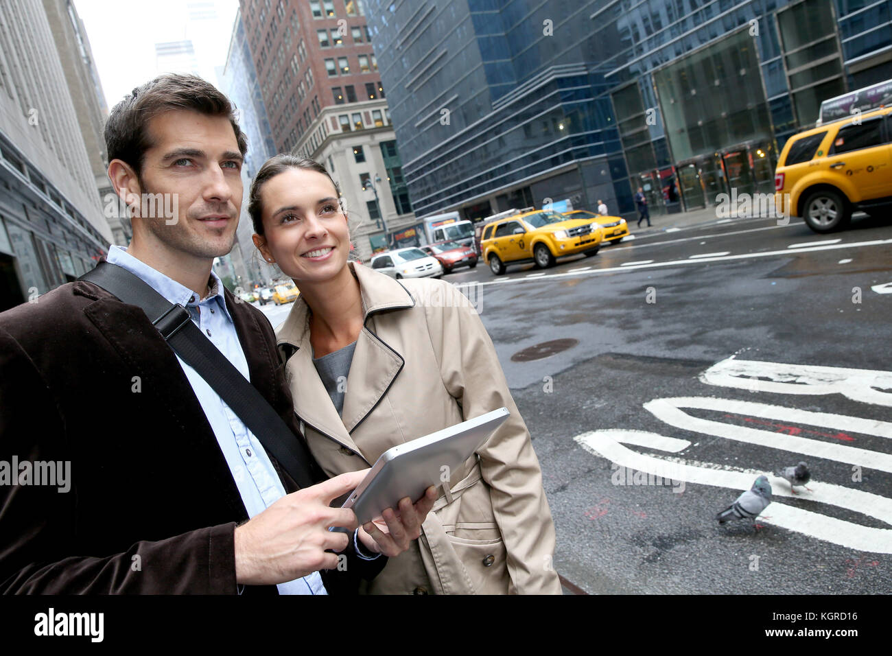 Business people using tablet in the street of Manhattan Stock Photo