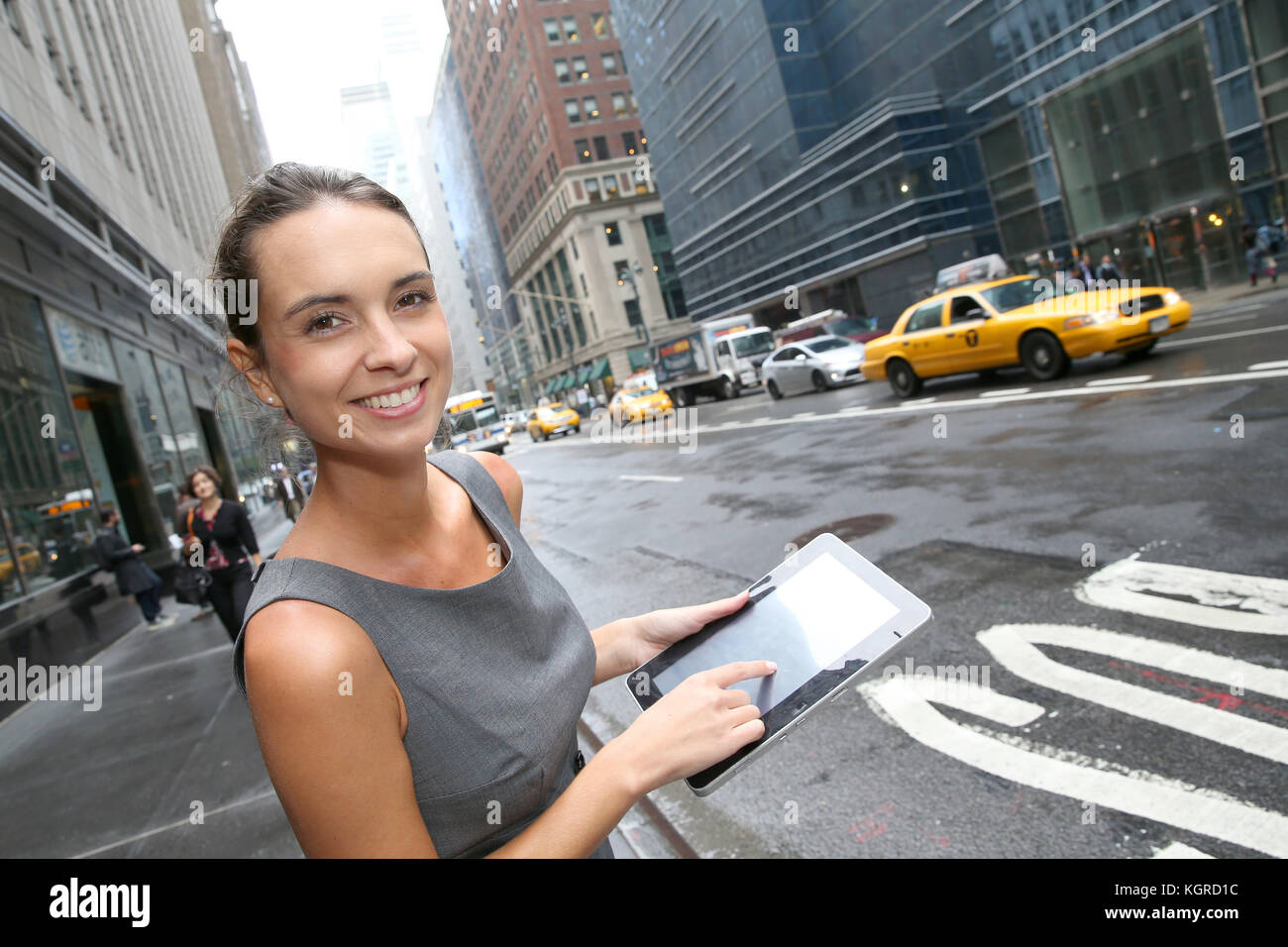 Businesswoman with tablet waiting for a taxi cab in NYC Stock Photo