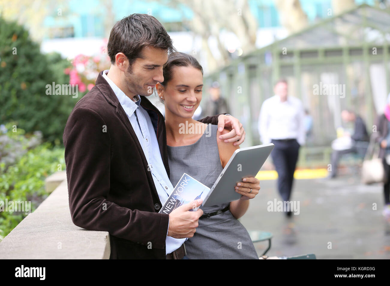 Couple of tourists in Bryant Park using tablet and city guide - Stock Image
