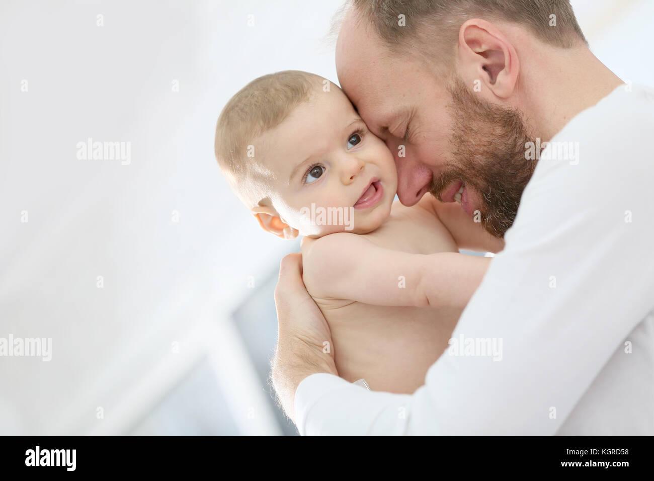 Portrait of daddy cuddling newborn son - Stock Image
