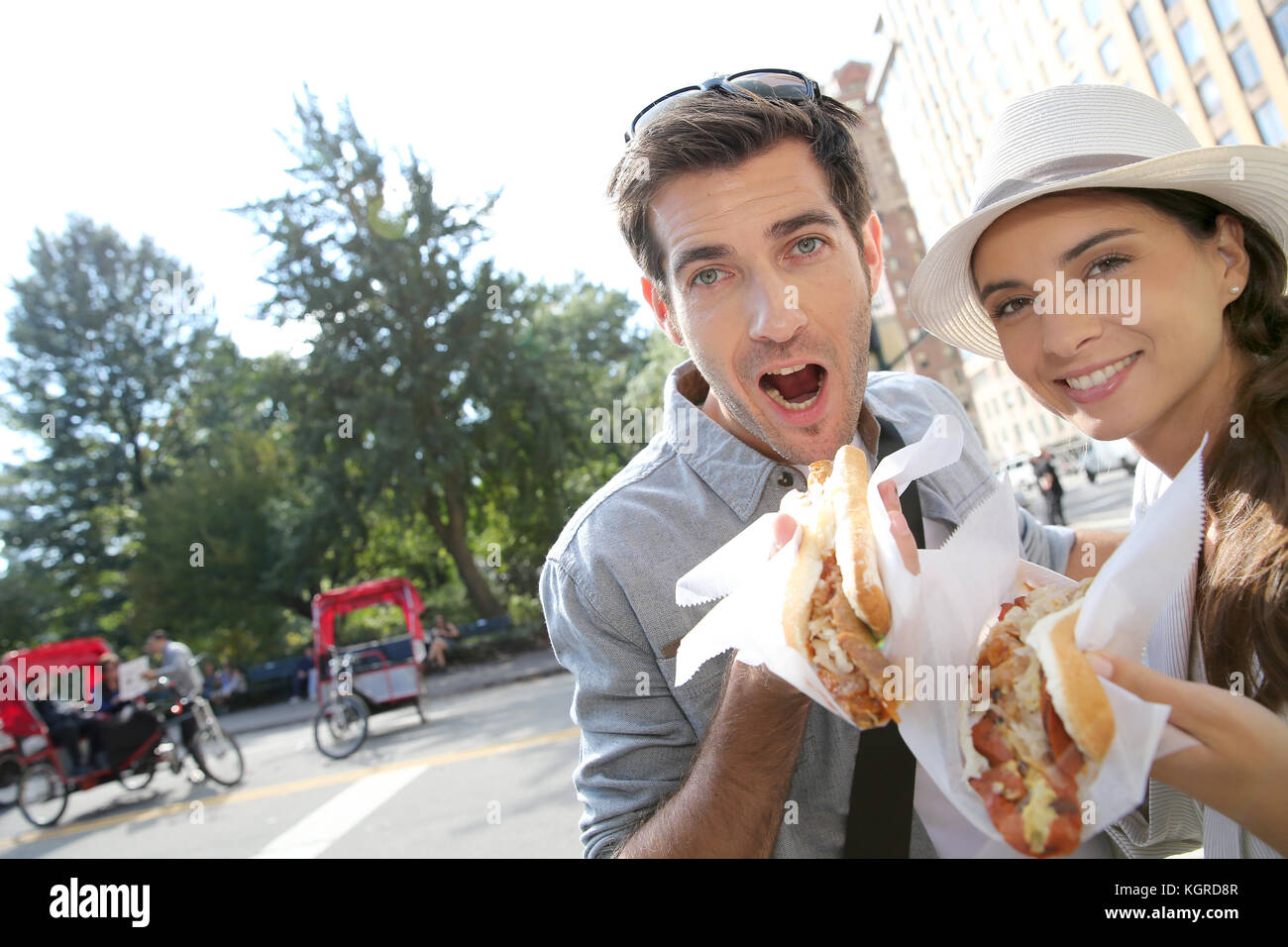 Tourists in New York city eating hot dogs - Stock Image