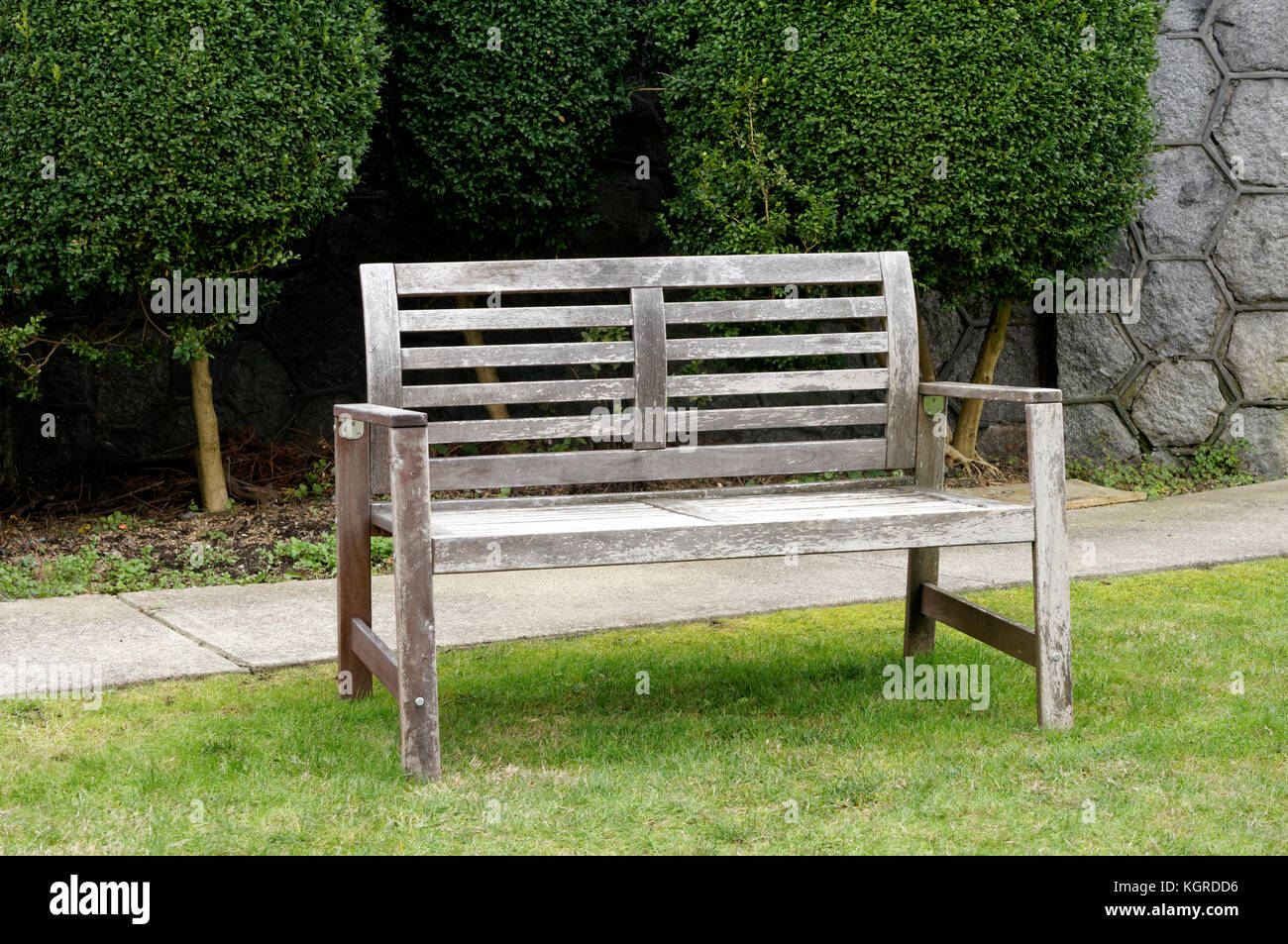 Unoccupied empty wooden bench on the front lawn of a house - Stock Image