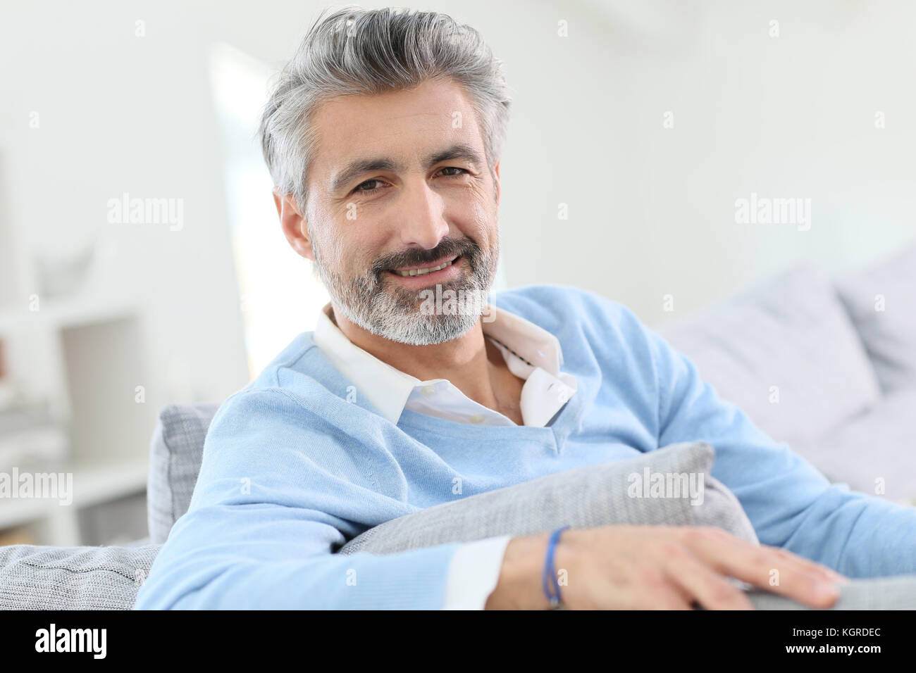 45-year-old man relaxing in sofa at home - Stock Image