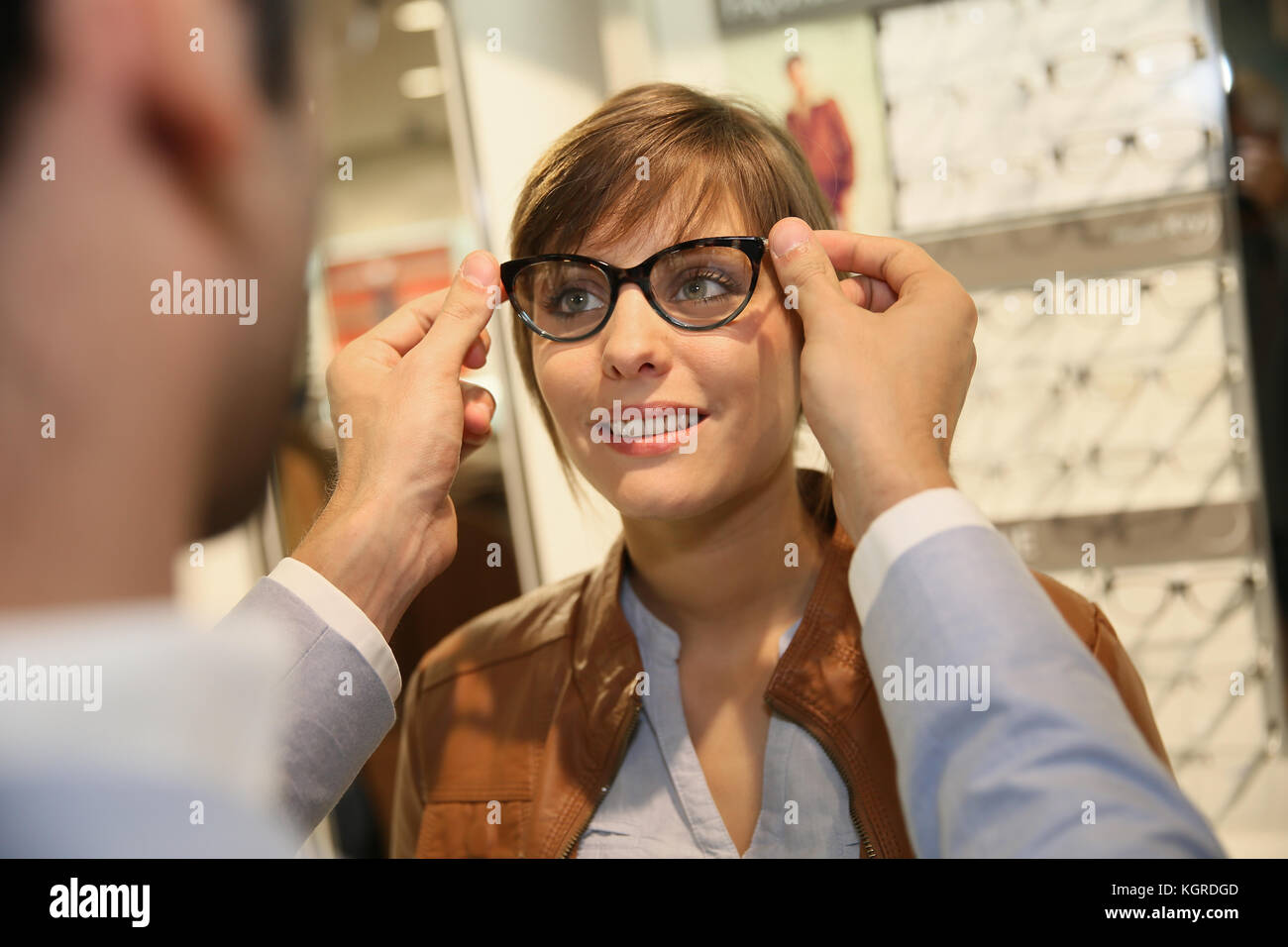 Young woman with optician in optical shop trying eyeglasses - Stock Image