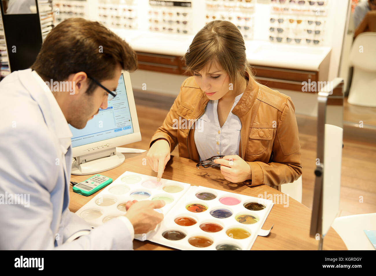 Woman with optician choosing spectacle lenses colour - Stock Image