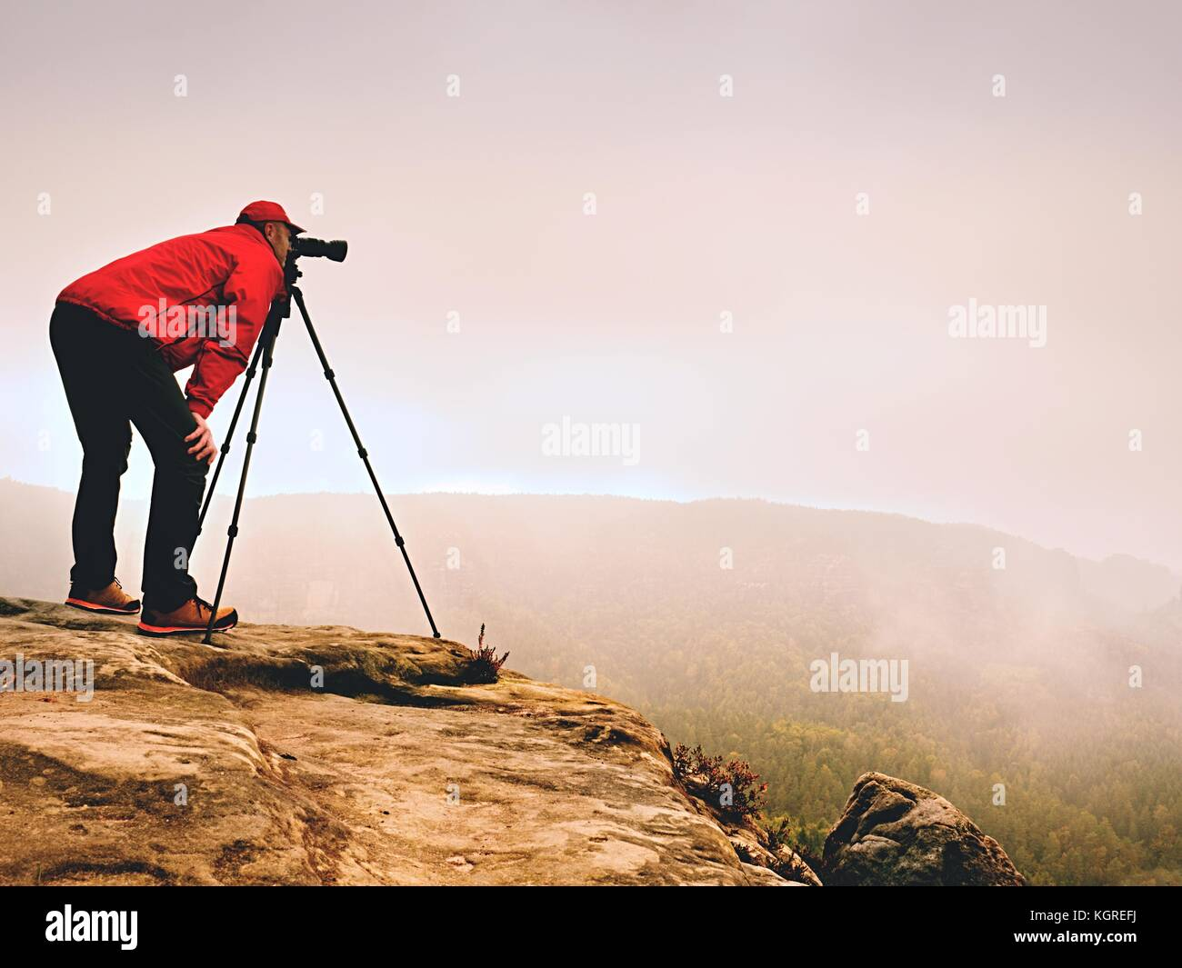 Professional photographer work on mountain peak. Nature photographer takes photos with mirror camera on rock above - Stock Image