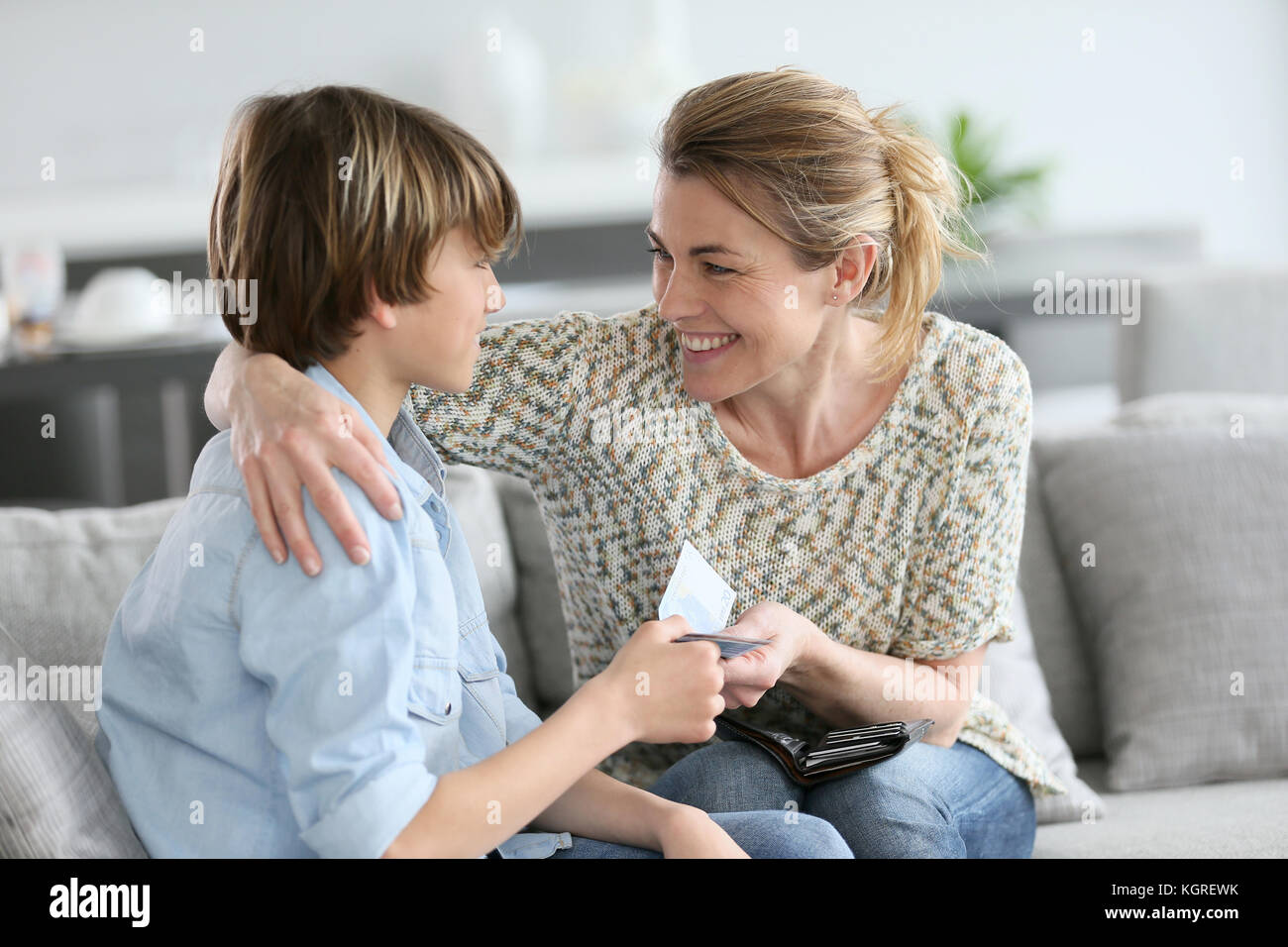 Mother giving money to adolescent for reward - Stock Image
