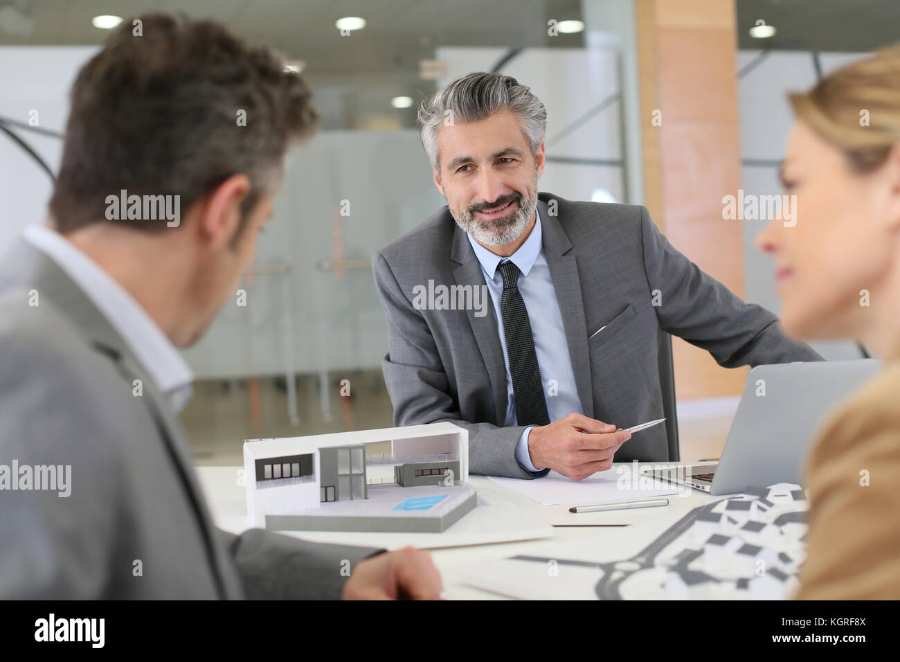 Architect meeting with clients in office - Stock Image