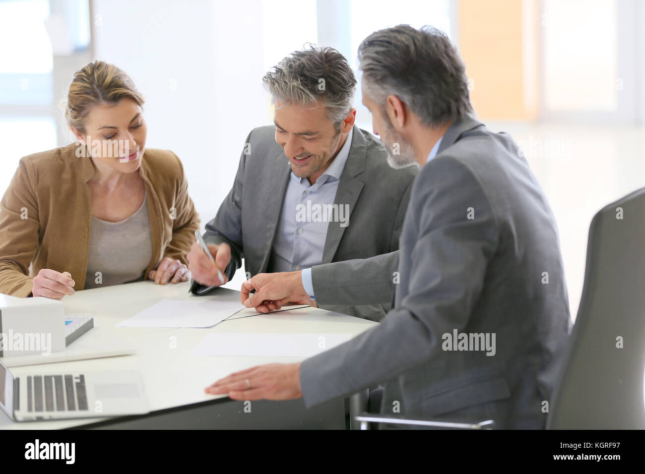 Mature couple signing construction contract in architect's office - Stock Image