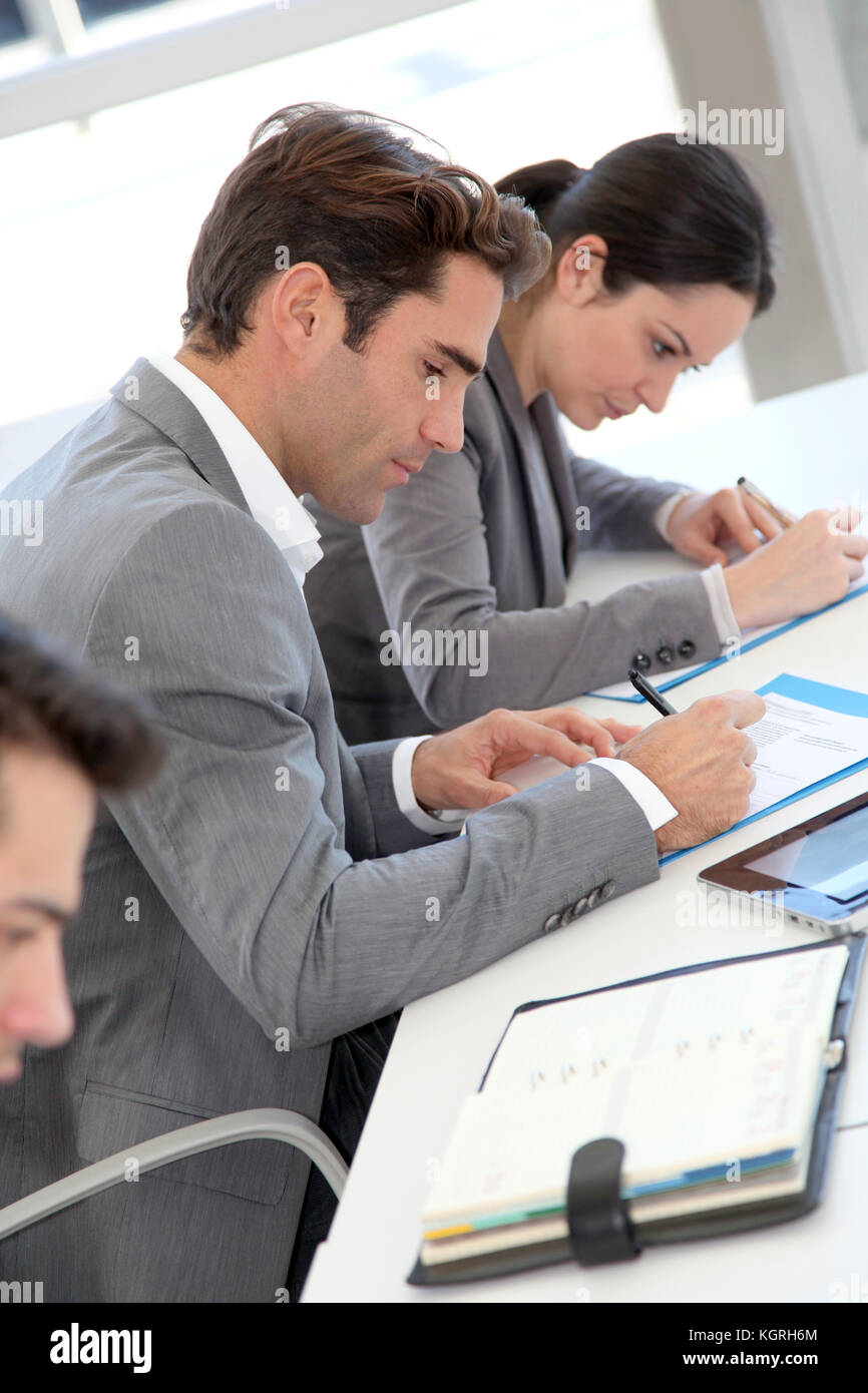 Young people signing application form - Stock Image