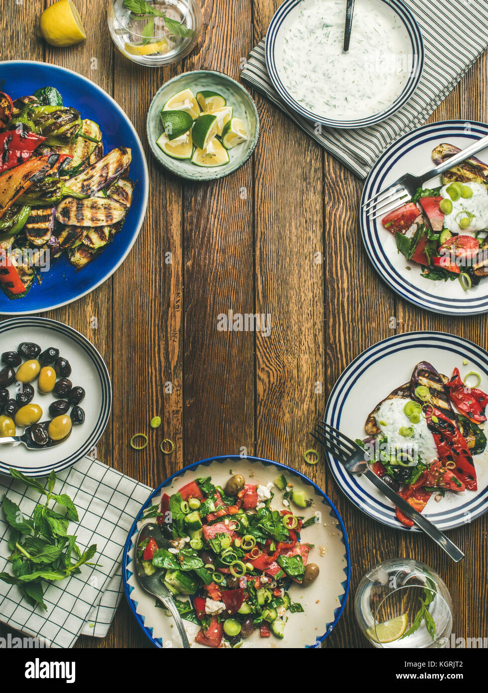 Flat-lay of healthy dinner table setting. Fresh salad, grilled vegetables with yogurt and dill sauce, pickled olives - Stock Image