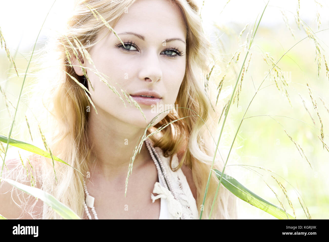 Glamorous young woman standing in meadow - Stock Image