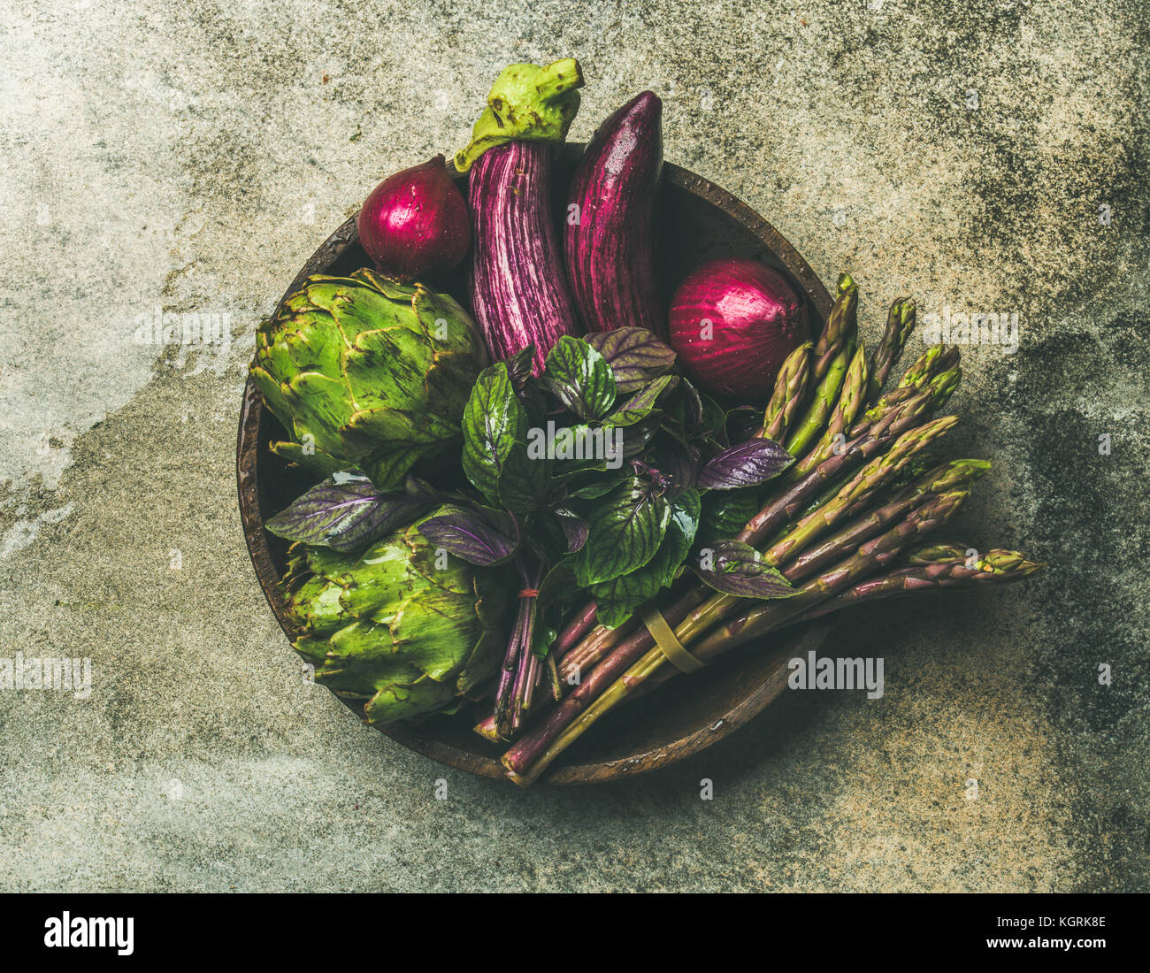 Flat-lay of green and purple vegetables on plate over grey background, top view. Local produce for healthy cooking. - Stock Image