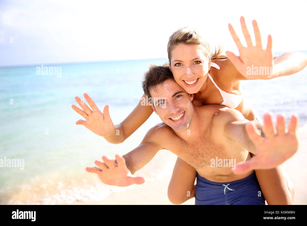 Man giving piggyback ride to girlfriend at the beach Stock Photo