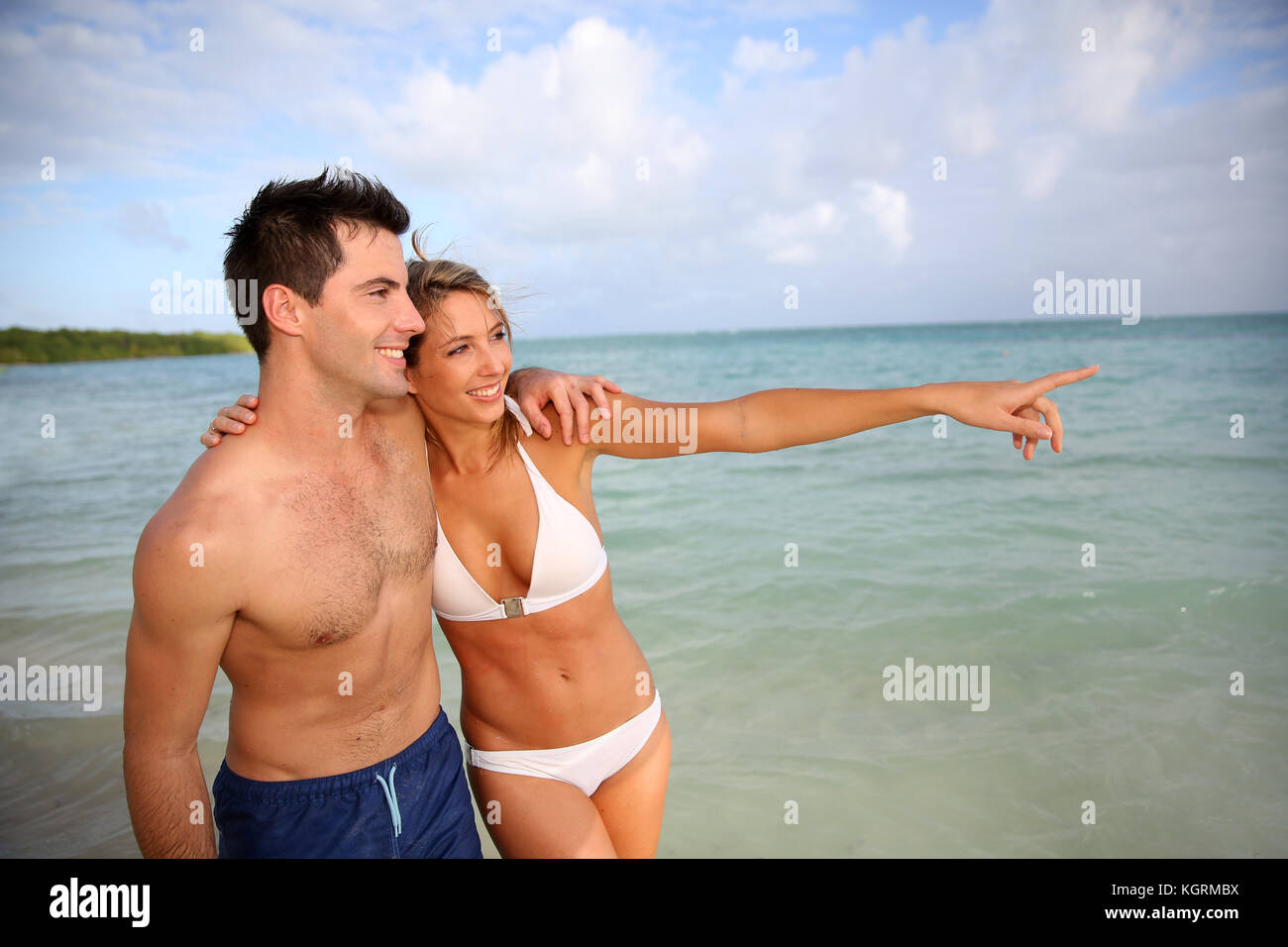 Couple walking by the beach in tropical island - Stock Image