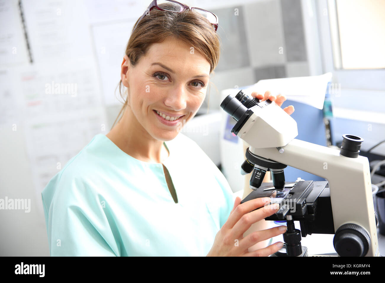 Doctor in laboratory looking through microscope - Stock Image