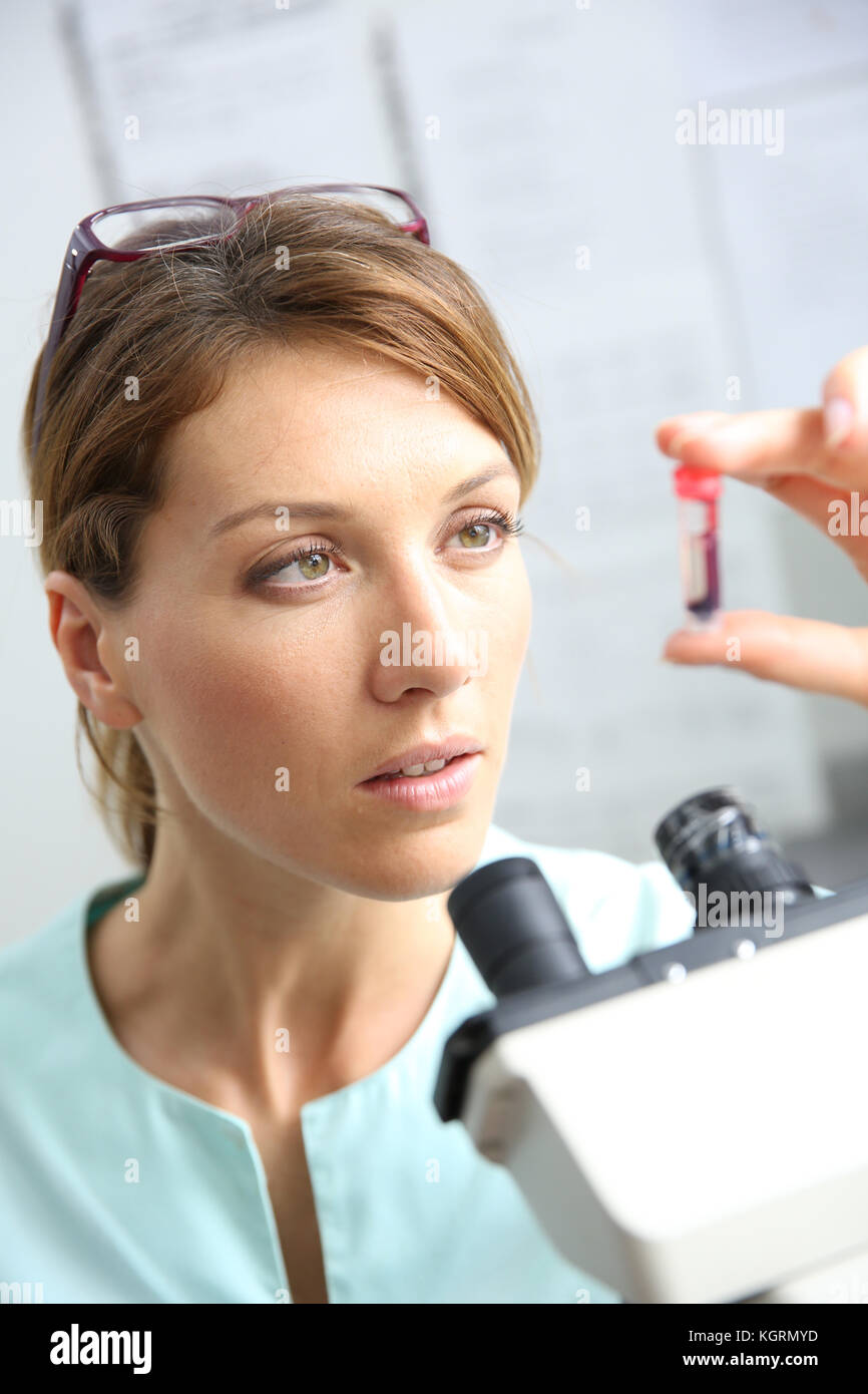 Biologist checking on blood sample - Stock Image