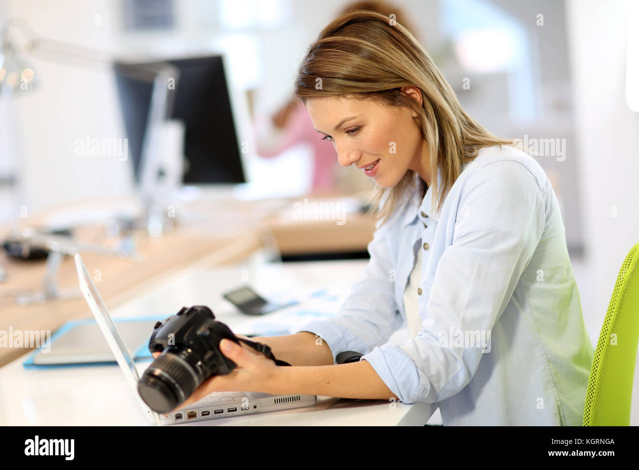 Woman reporter in office looking at photo camera - Stock Image