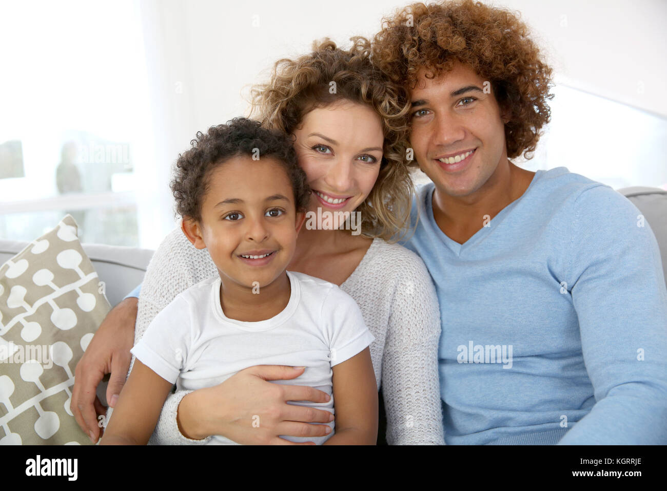 Portrait of happy family sitting in couch - Stock Image