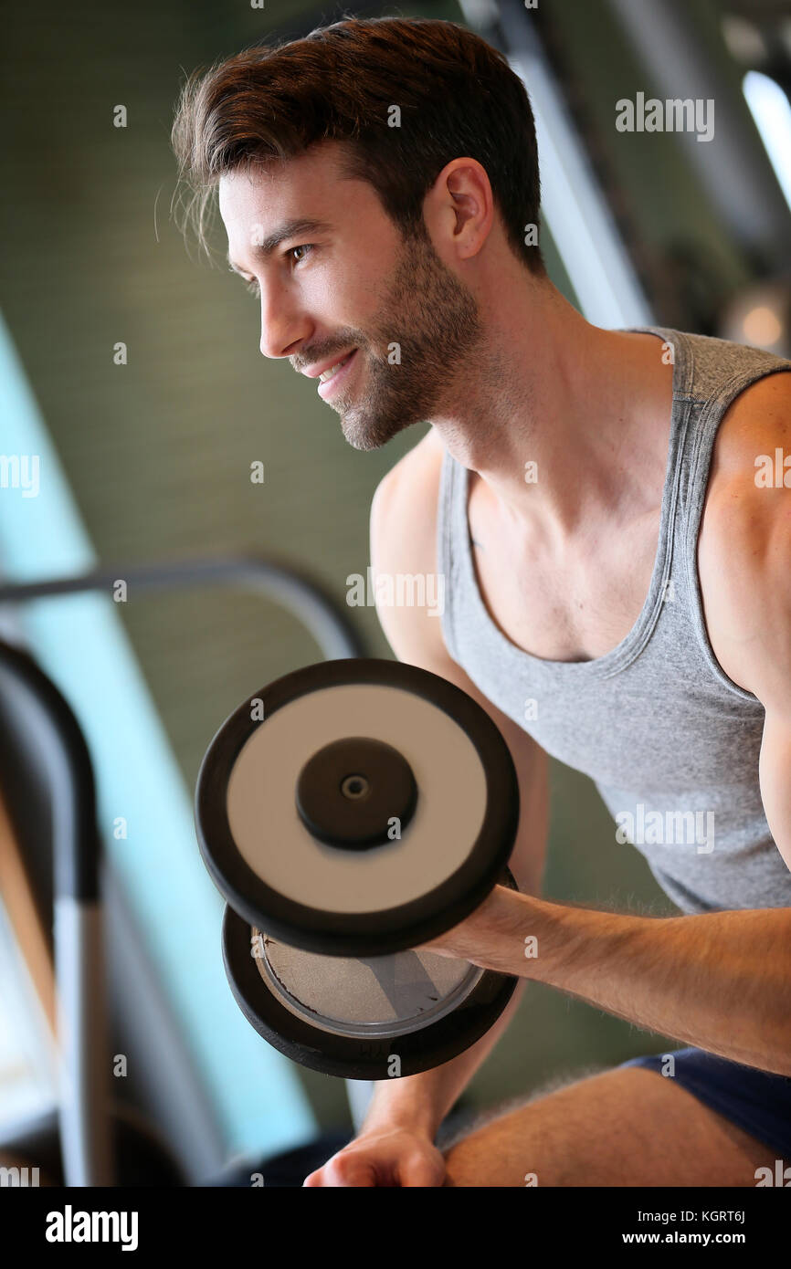 Man lifting weights in fitness center - Stock Image