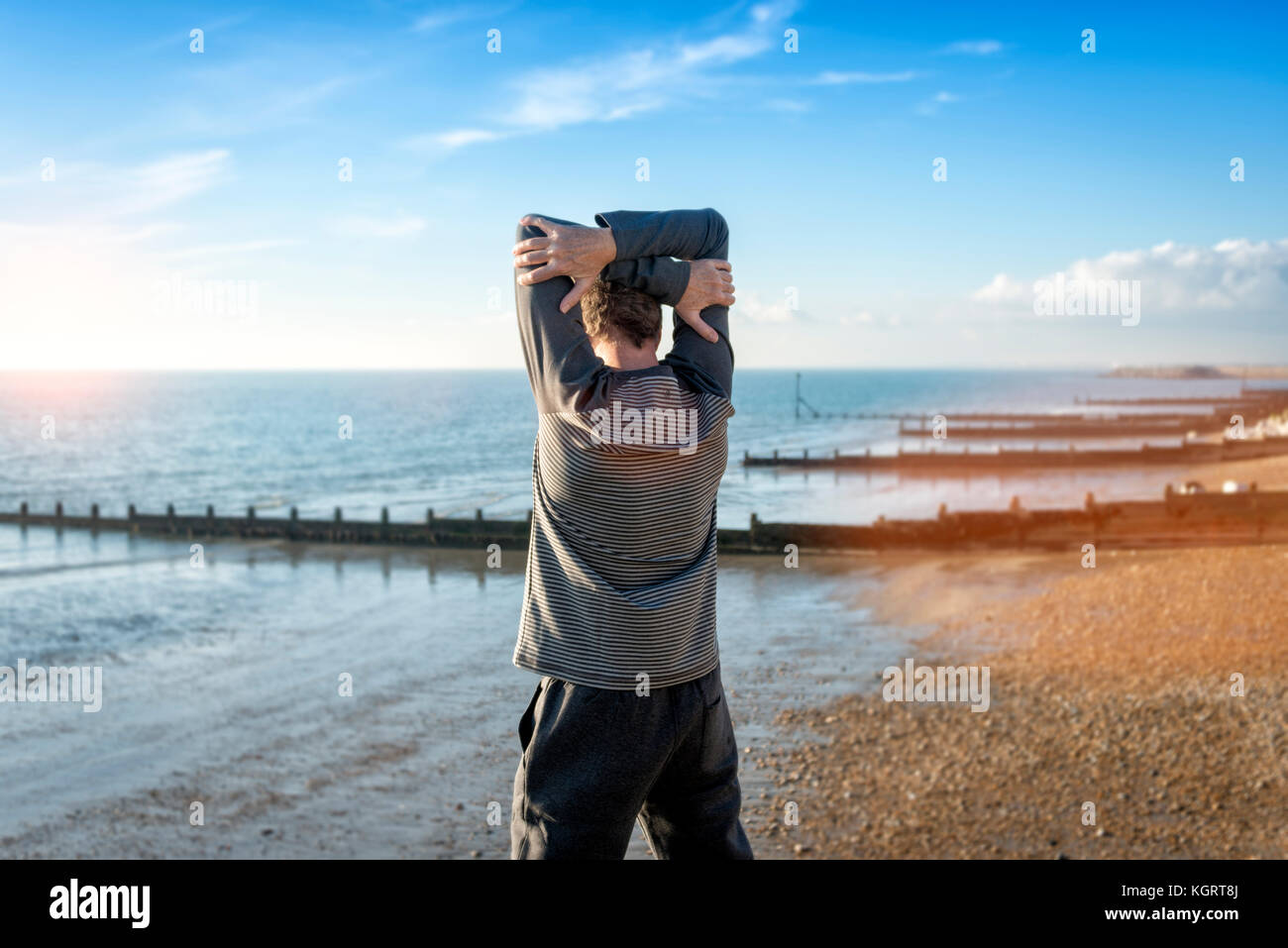 man stretching by the sea, warming up before exercise training. - Stock Image