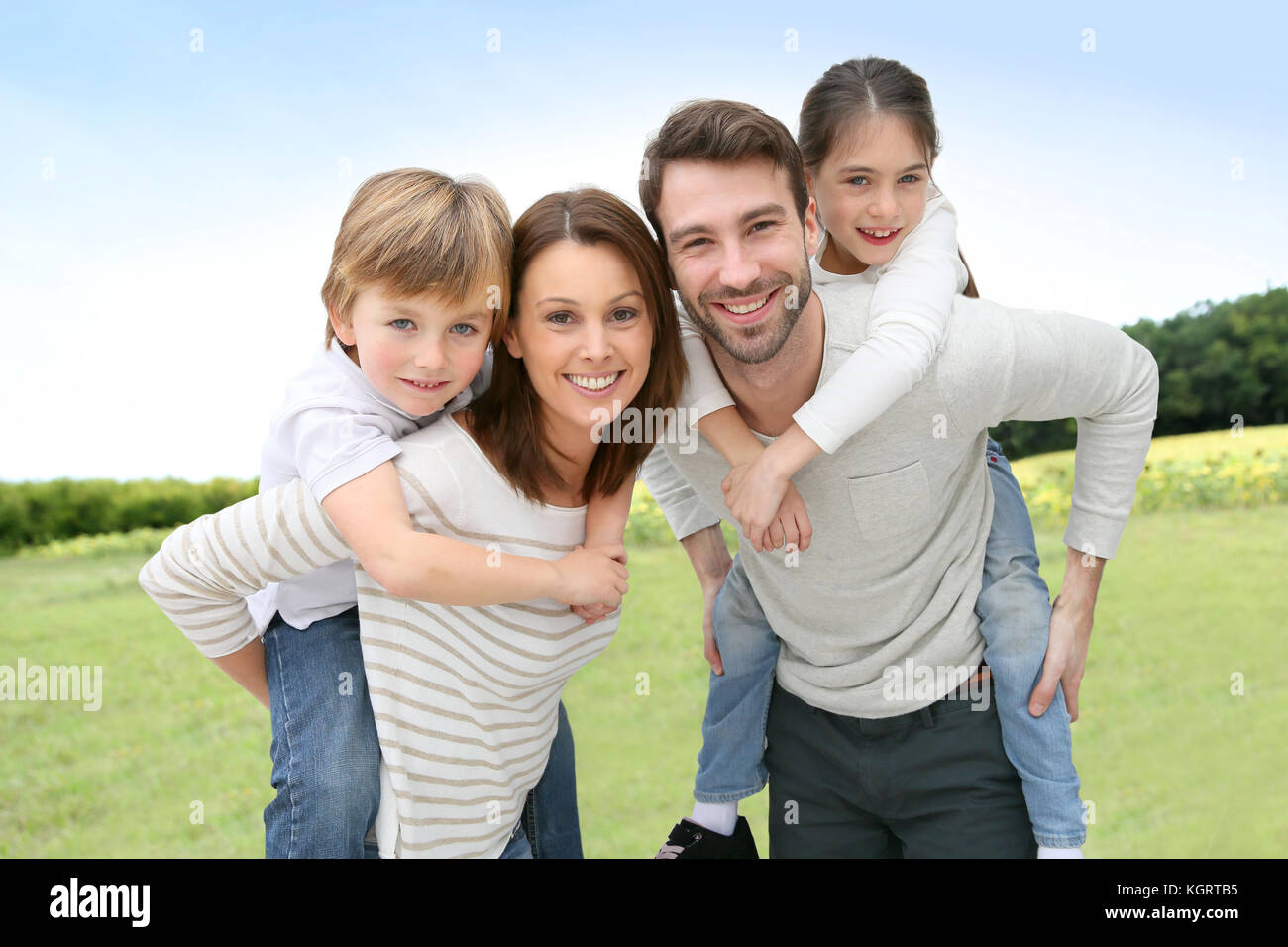 Young parents giving piggyback ride to kids - Stock Image