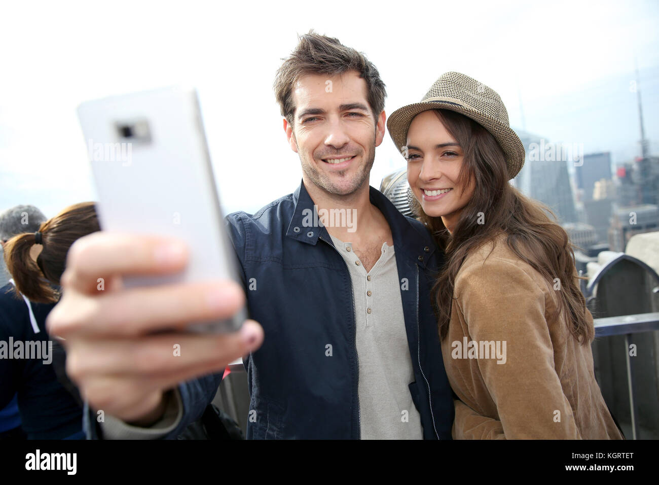 Couple taking picture with smartphone, skyline in background Stock Photo