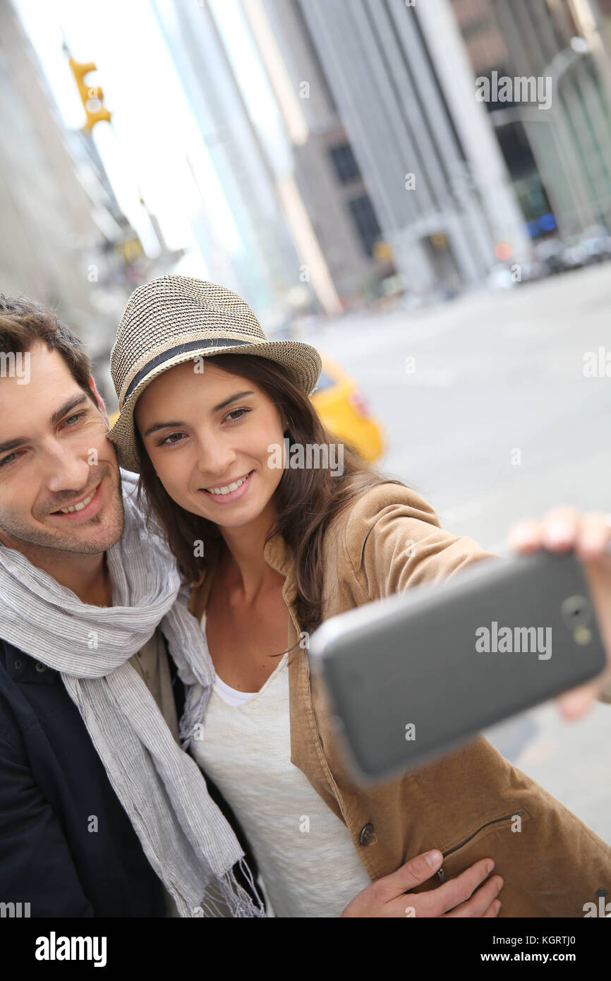Couple in Manhattan taking picture with smartphone - Stock Image