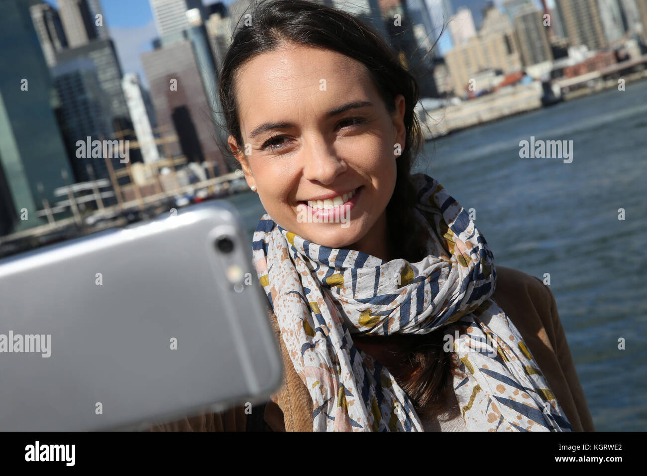 Brunette girl making selfy with Manhattan in background - Stock Image