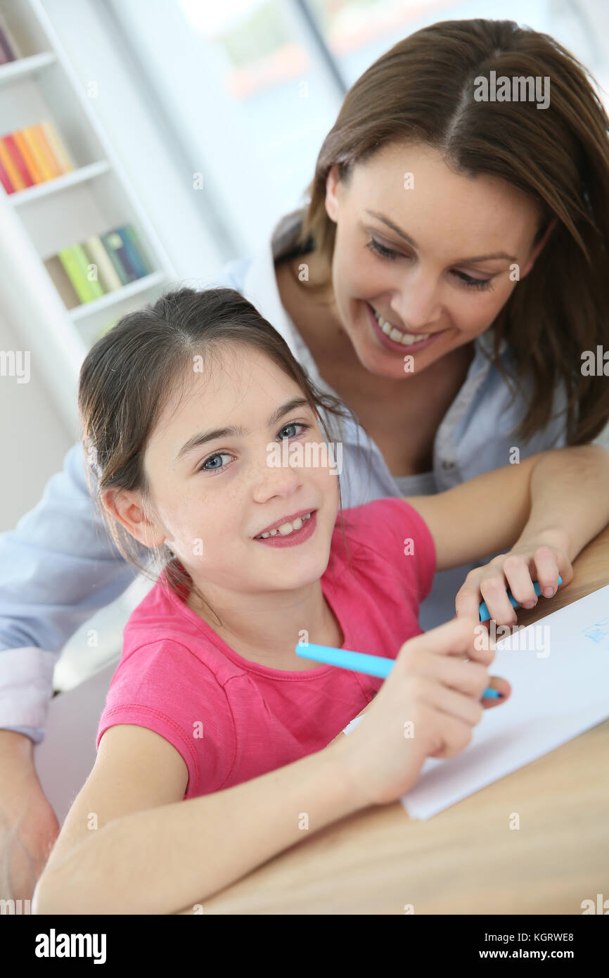 School girl with mother learning to write - Stock Image