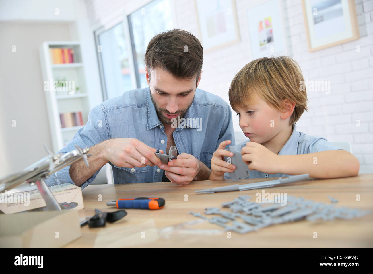 Father and son assembling airplane mock-up - Stock Image