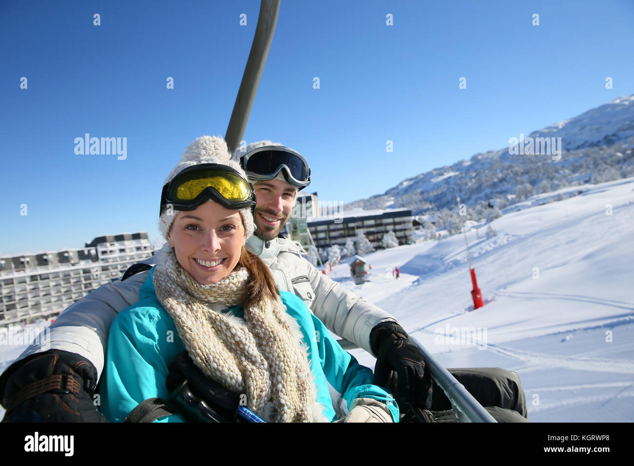 Couple sitting on ski resort chairlift - Stock Image