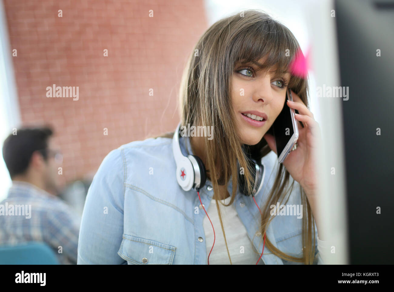 Young woman talking on smartphone in front of desktop - Stock Image