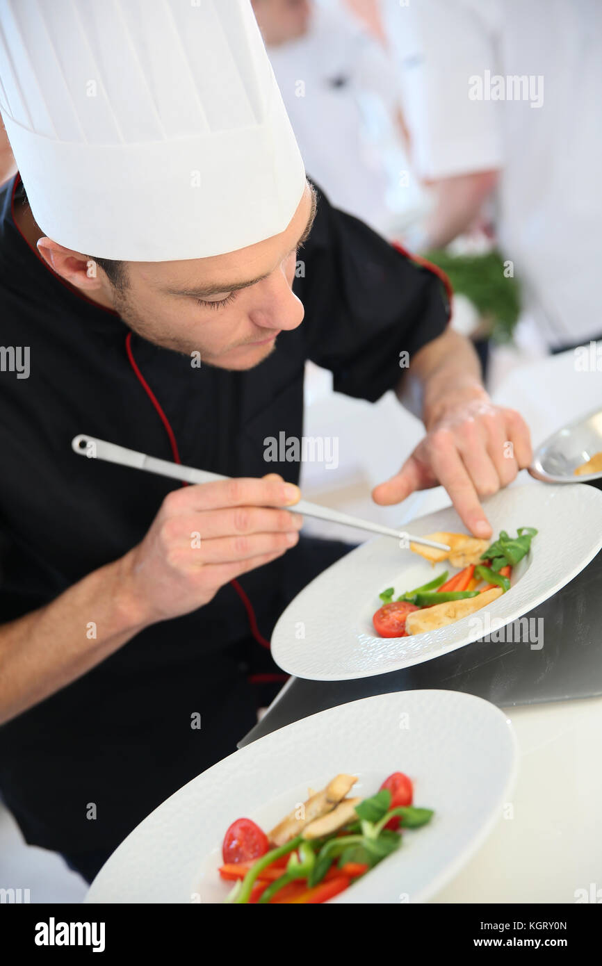 Chef in restaurant kitchen preparing dish - Stock Image