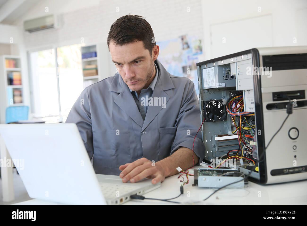 Technician fixing computer hardware - Stock Image