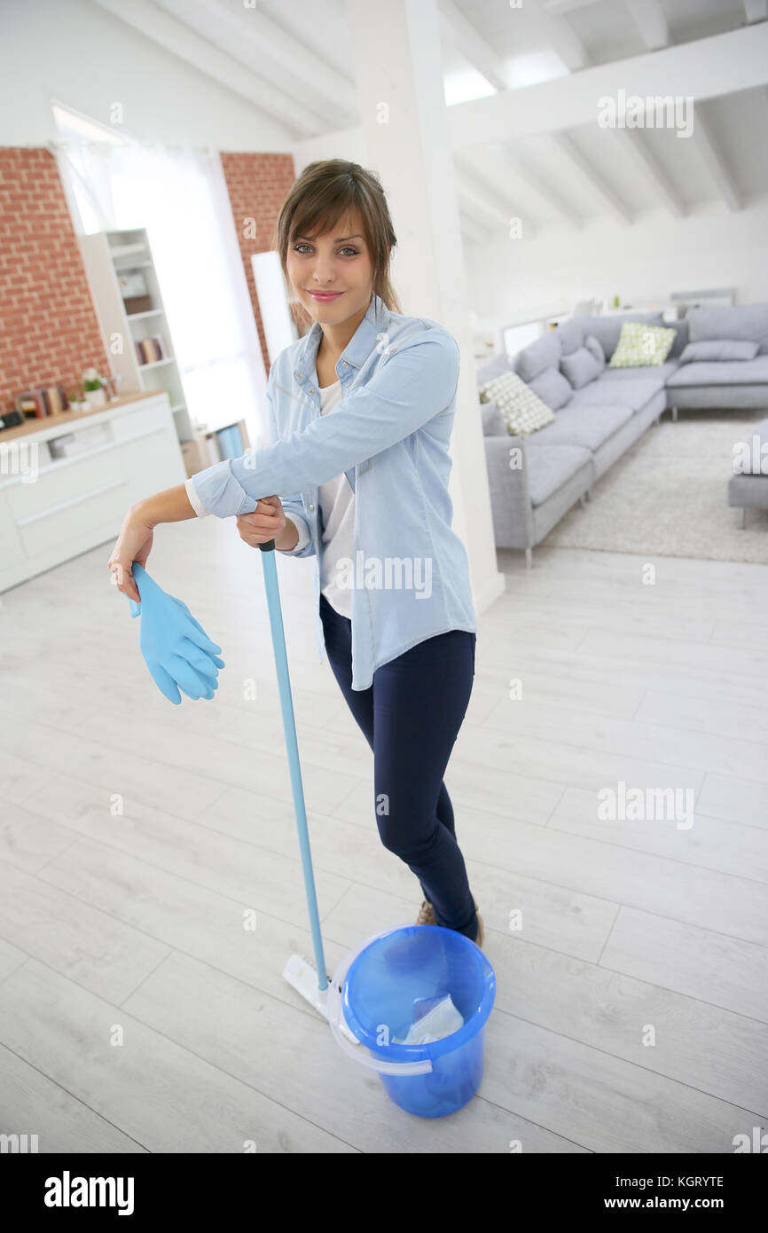 Young housekeeper standing with mopping equipment Stock Photo