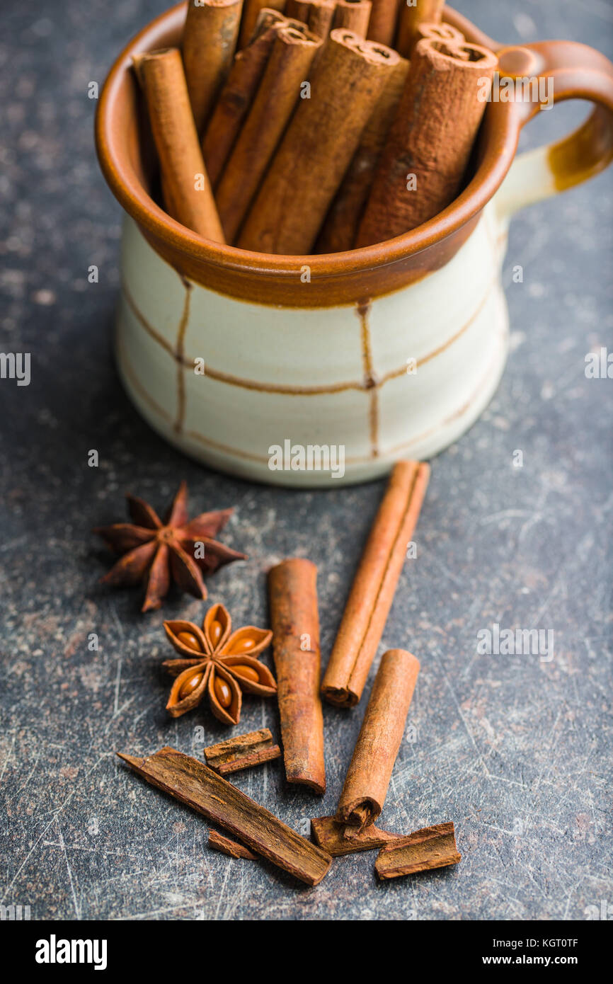 Cinnamon sticks and anise star on old kitchen table. - Stock Image