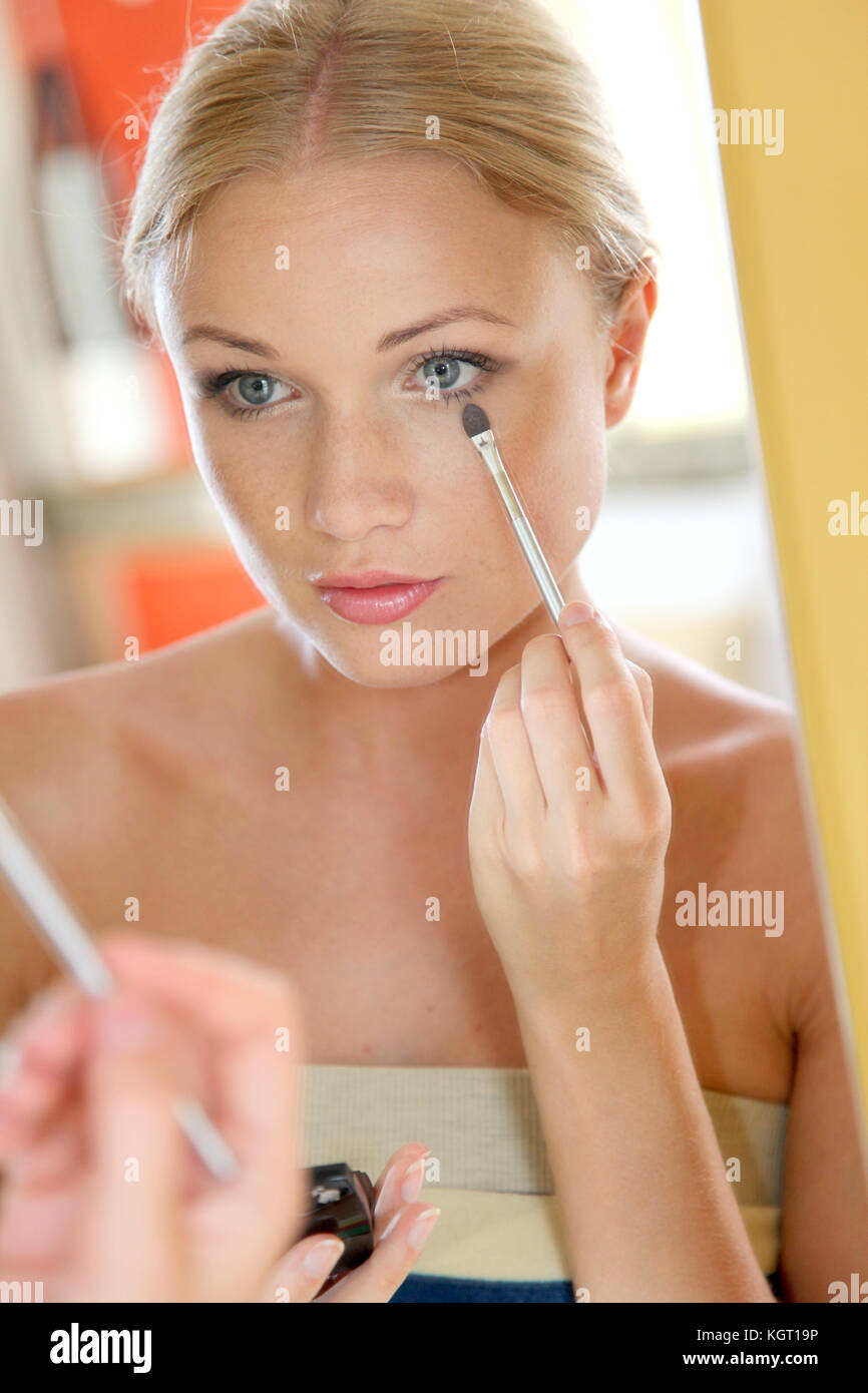 Portrait of beautiful woman applying eyeshadow - Stock Image