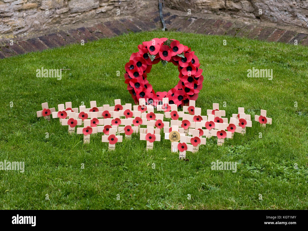 Remembrance Day Poppy Wreath and crosses in a town churchyard. - Stock Image