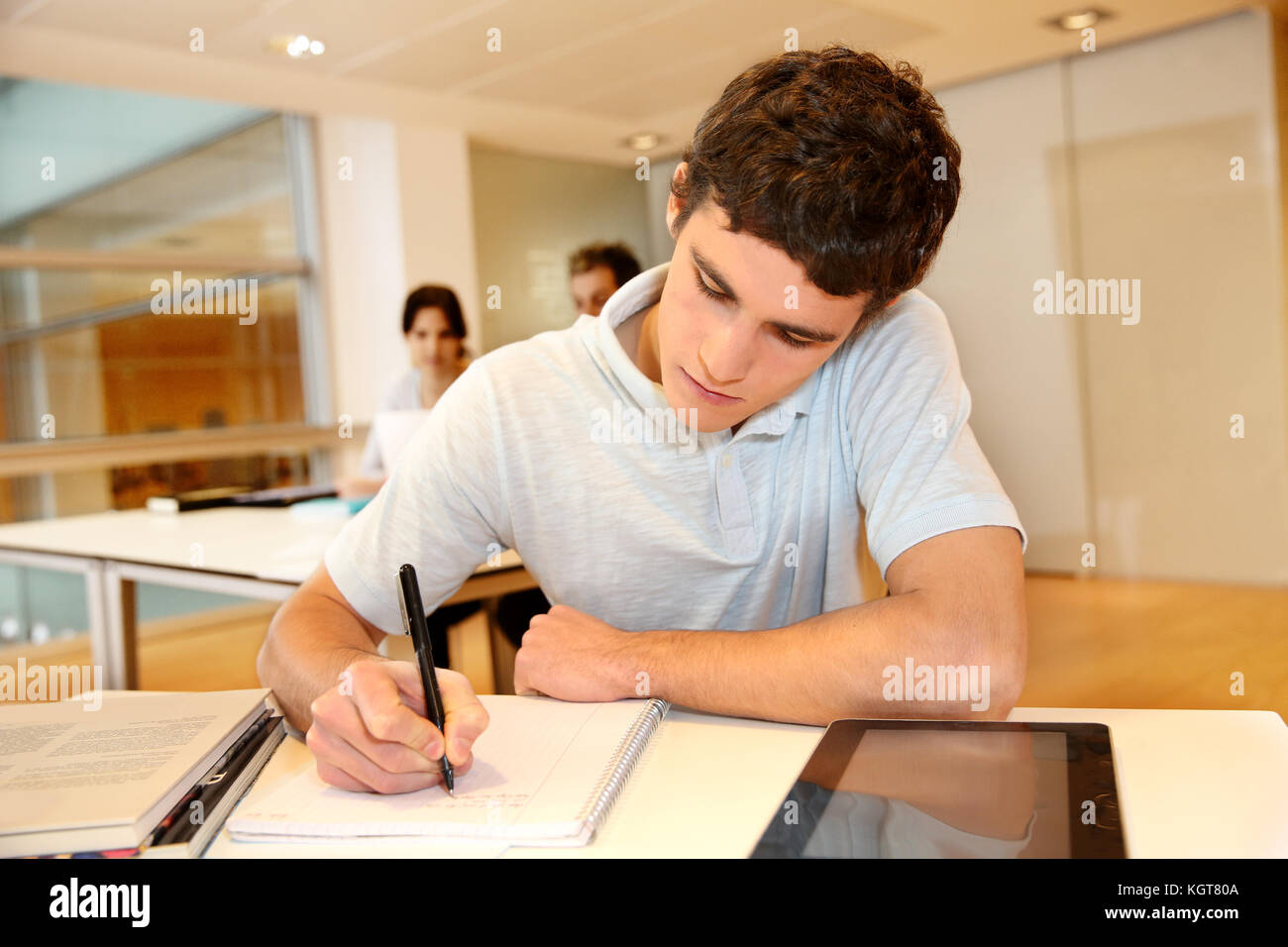Portrait of student boy writing on notebook - Stock Image