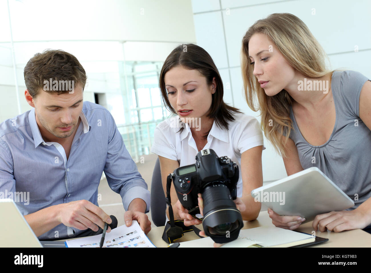 Team of photo reporters working in office - Stock Image