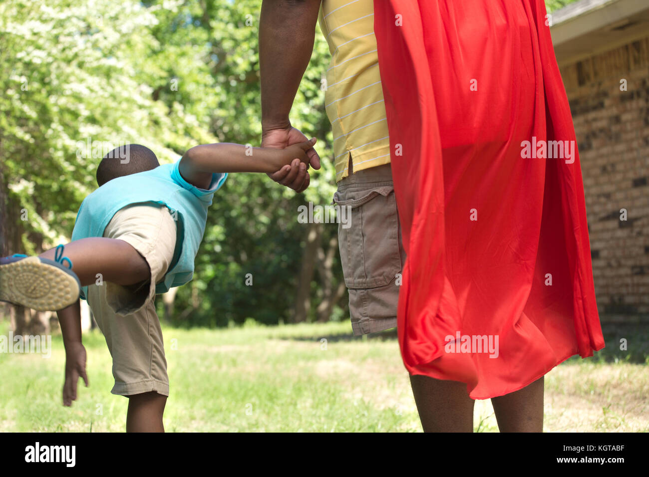 Little boy with his super hero father. - Stock Image