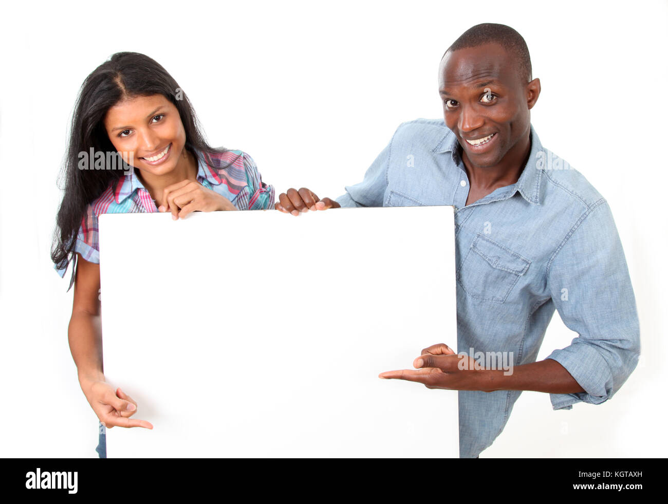 Cheerful couple showing message on whiteboard - Stock Image
