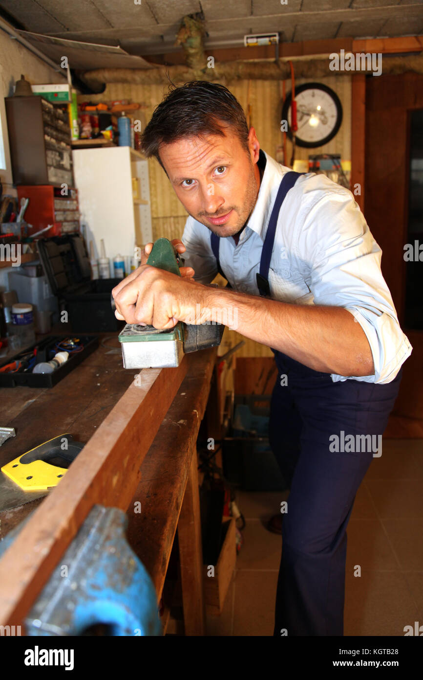 Joiner working wood in workshop - Stock Image